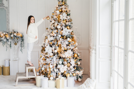 Indoor shot of adorable little kid stands on chair on tiptoes, decorates big New Year tree, has good mood, being in anticipation of holidays and wants to recieve presents. Celebration and decoration Stock Photo