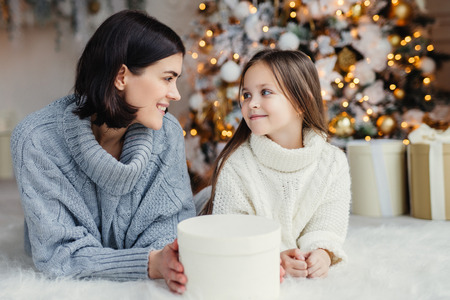 People, family, celebration and holidays concept. Mother and daughter with attractive appearance look at each other`s eyes, lie on warm white carpet near decorated New Year tree and gift box