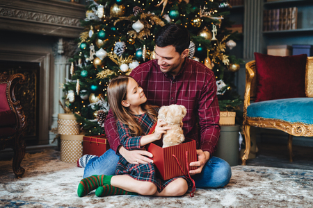 Small female child holds teddy bear, recieves unexpected gift from affectionate father, being thankful to him. Young dad gives present to daughter, congratulates her with Christmas or New Year