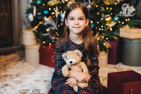 Small female child with appealing appearance, holds teddy bear, recieves present from parents, sits near Christmas tree. Adorable girl being glad to get gift on New Year. Christmas time.