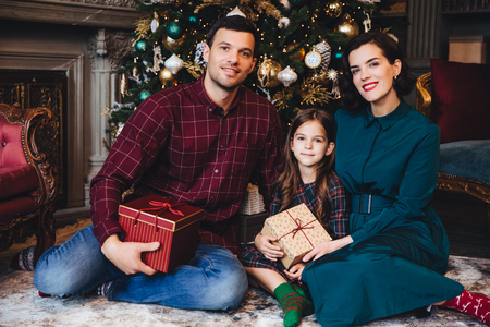 Father, mother and daughter enjoy holidays together, smile happily as sit in living room near decorated New Year tree, hold present wrapped in boxes, look delightfully into camera. Family concept