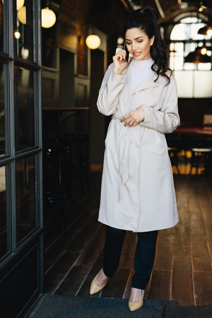 Full length portait of elegant businesswoman wearing white overcoat, stylish shoes and black trousers standing in cafe calling her business partner while waiting for him. People, technology concept