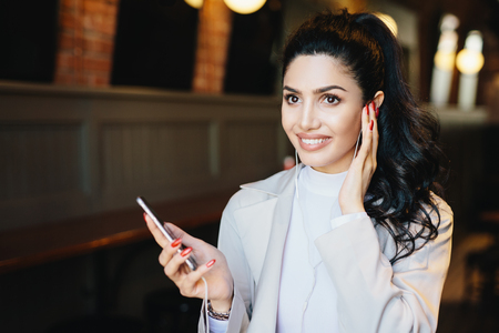 Beautiful brunette woman with expressive eyes and long eyelashes, having make-up and red manicure wearing white jacket listening to her favourite audio book having happy expression sitting indoors Stock Photo