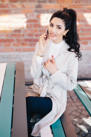 Adorable brunette woman in white coat and black trousers sitting indoors over brick wall talking on cellphone with her man discussing their date and remembering pleasant moments. Technology concept
