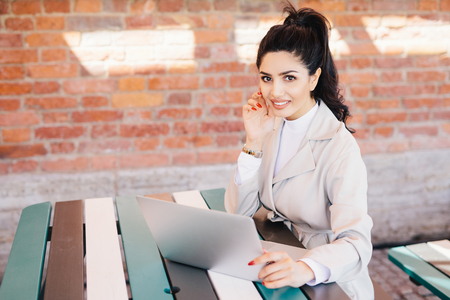 Succsessful businesswoman with dark hair, nice eyes, healthy skin, well-shaped lips having red long nails wearing formal clothes while sitting at cafe using laptop for online communication and work