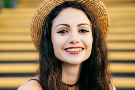 Cheerful woman with dark eyes, pure skin, red lips and long dark hair wearing straw summer hat looking with delightful expression.
