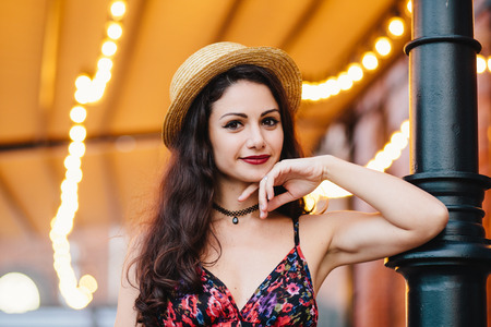 Gorgeous young elegant woman with appealing appearance posing at terrace, dressed in straw hat and summer dress, keeping her hand on chin, having confident look, looking directly into camera Stock Photo