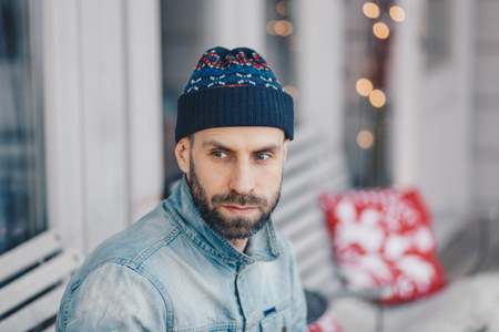 Good looking European male with thick beard and mustache wears hat and denim jacket, has thoughtful expression, contemplates about something, poses indoor. Pensive young bearded stylish man.