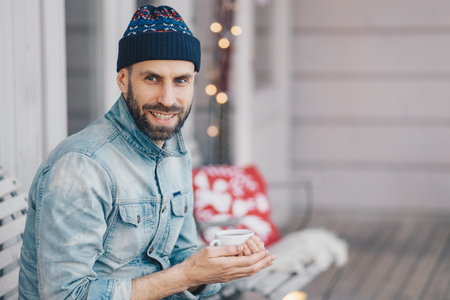 Positive bearded stylish male with pleasant smile, wears fashionable hat and jean jacket, holds cup of aromatic coffee, spends free time at balcony, breathes fresh air, thinks about something