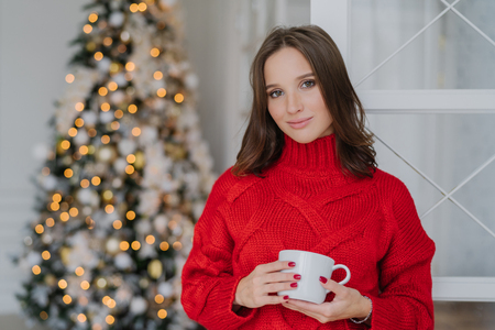 Beautiful woman with pleasant appearance and makeup, wears warm knitted winter sweater, holds mug of coffee, stands near decorated New Year tree, plans how to celebrate holiday. Rest concept