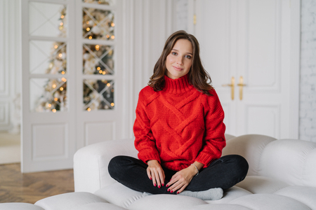 Photo of calm carefree girl wears warm doemstic clothes, poses on white couch, looks directly at camera, spends winter weekend at home, anticipates New Year, decorated fir tree. Holidays concept