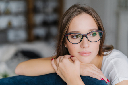 Thoughtful dark haired European female in spectacles looks aside, leans at back of couch, contemplates about future, feels lonely, enjoys domestic atmosphere, poses against blurred background
