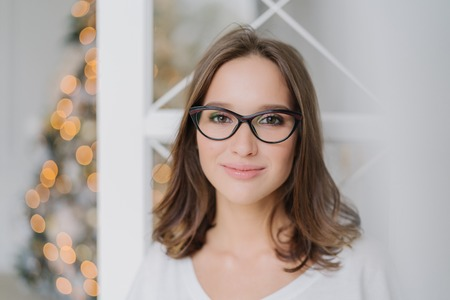 Close up shot of good looking young female model wears spectacles for good vision, looks happily at camera, has pleased expression, charming smile, poses against decorated Christmas tree indoor