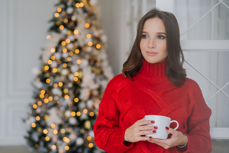 Photo of thoughtful female model wears red sweater, drinks tea, has dark hair, contemplates about something, stands in spaciouss room near decorated new Year tree with lights. Holiday concept 版權商用圖片