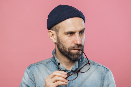 Portrait of pensive bearded man takes off glasses, wears denim stylish jacket and hat, isolated over pink background. Middle aged unshaven male contemplates about something, looks concentrated Banco de Imagens