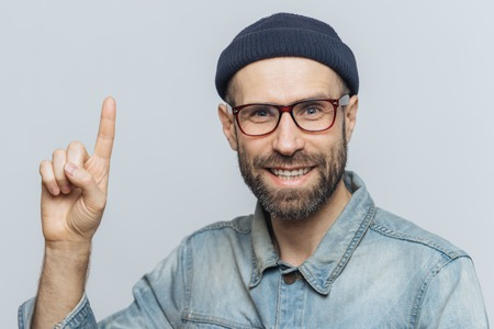 Positive handsome bearded male raises fore fimger, looks with cheerful expression directly intto camera, wears fashionable hat, shirt, raises fore finger as remebers something, models indoor