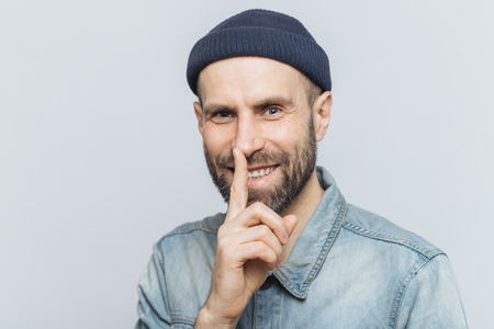 Cheerful attractive male with blue eyes shows silence sign, has satisfied expression, wears fashionable hat and denim jacket, isolated over grey background. Handsome man shows hush sign. Be quiet!
