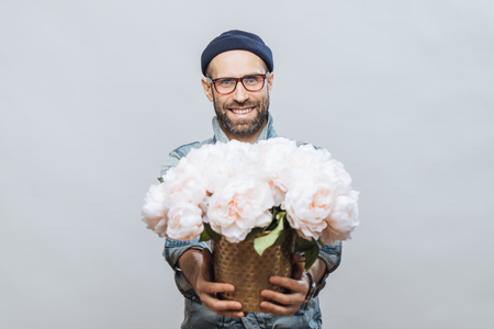 These flowers are for you! Glad smiling bearded male stretches hands while holds bunch of white beautiful flowers, makes present for someone, isolated over studio background, has date with girlfriend