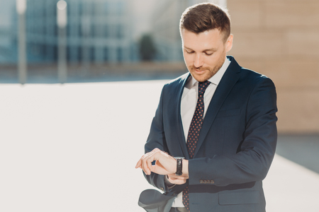 Handsome attractive male checks time, hurries for business meeting, looks at watch, dressed in formal black suit, poses outdoor near office building. People, business and occupation concept. Reklamní fotografie
