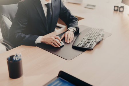 Cropped image of successful male business owner sits at work place in formal suit, uses computer for work, prepares financial report. Male executive works in office alone. People and finances