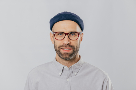 Headshot of handsome unshaven man wears transparent glasses, headgear, formal shirt, looks directly at camera, isolated over white background. Caucasian male with stubble dressed in fashionable outfit