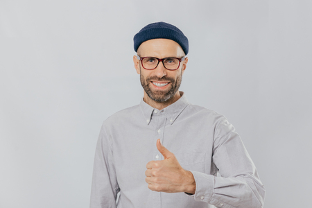Positive smiling man with stubble, raises thumb up, demonstrates his like and approvement, wears headgear and formal shirt, isolated over white background. My answer yes. Gesturing. Body language Banco de Imagens