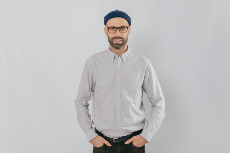 Indoor shot of satisfied Caucasian man in spectacles with bristle, keeps hands in pockets, dressed in formal stylish clothes, has gentle smile, happy to be promoted, isolated over white background. Stock Photo