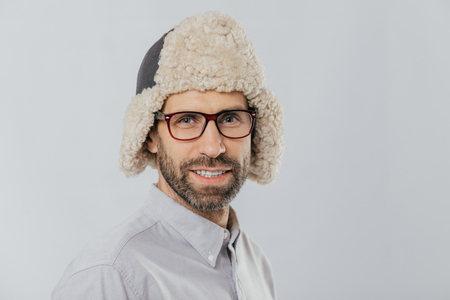 Photo of attractive young European male with pleasant appearance, wears warm fut hat, transparent glasses, models over white studio wall, rejoices shopping during weekend. People, style concept Stock Photo