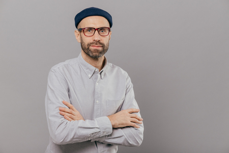 Photo of serious male keeps arms folded over chest, dressed in white formal shirt, fashionable hat, poses for making photography over grey wall with free space for your advertisement or promotion