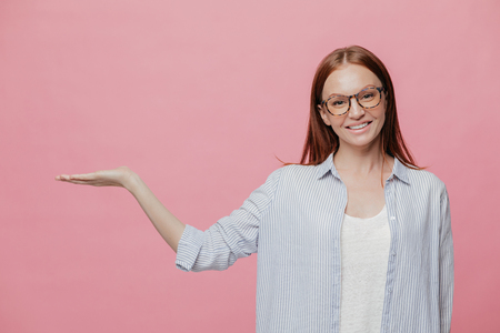 Positive young smiling woman raises hand, pretends holding something, gestures over copy space, dressed in sylish oversized shirt, wears spectacles, isolated over pink studio wall. Advertisement