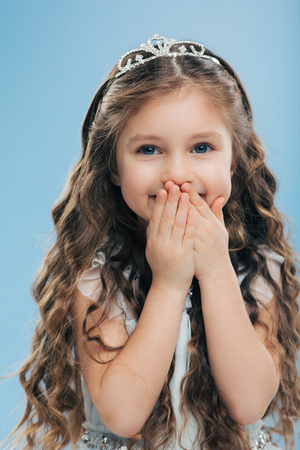 Image of positive beautiful smiling child keeps both hands on mouth, has long thick hair, blue eyes, wears crown, poses against blue background, expresses happiness. Children and satisfaction