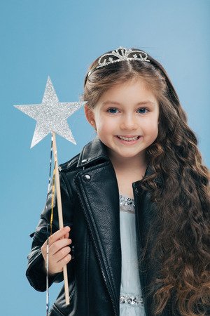 Satisfied small female child has long curly hair, dressed in black leather jacket, wears crown, holds magic wand, isolated over blue background. Dark haired positive kid anticipates for miracle Banco de Imagens - 116473298