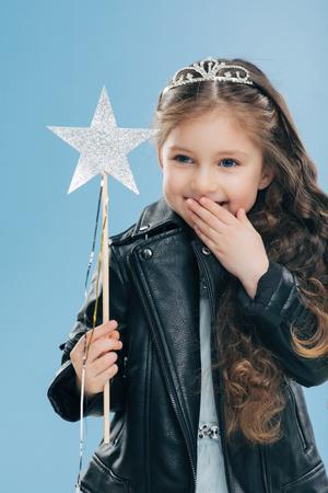 El niño pequeño de aspecto agradable y alegre cubre la boca con la palma, se ríe positivamente, usa corona y chaqueta de cuero negro, sostiene una varita mágica, aislada sobre fondo azul. Los niños y el concepto de felicidad.