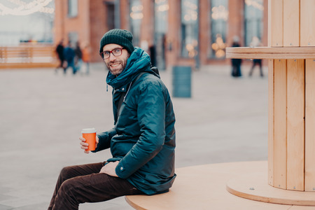 Horizontal view of cheerful European man with thick bristle, wears hat and jacket, holds disposable cup of coffee, breathes fresh air, poses at street. Male model enjoys fresh beverage outside