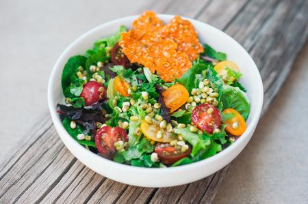 Concetto di cibo sano. Insalata fresca di pomodorini, fagioli verdi, patatine di carota e pane piatto su fondo di legno. Insalata di verdure verdi per cena