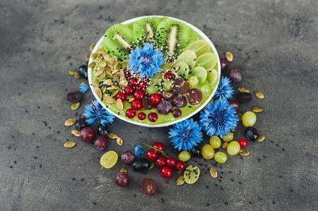 Bowl with fresh kiwi salad, seeds, red current, green grape and blue cornflowers around. Vegeterian dish of ripe fruit. Top view. Blank space