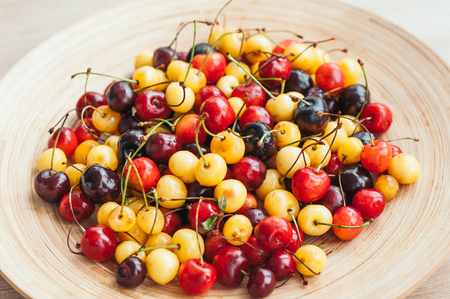 Image of fresh ripe cherries on bowl. White and red cherries. Healthy eating. Seasoanl fruits. Nutrition concet. Raw food