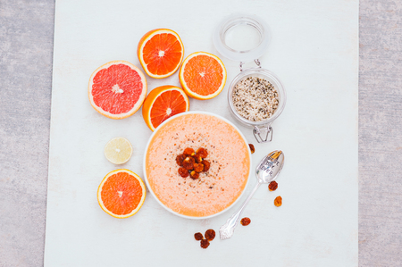 Smoothie bowl with slices or orange, lime or grapefruit, hempseed, spoon. Dry golden berry. Isolation on white background. Organic food. Stockfoto