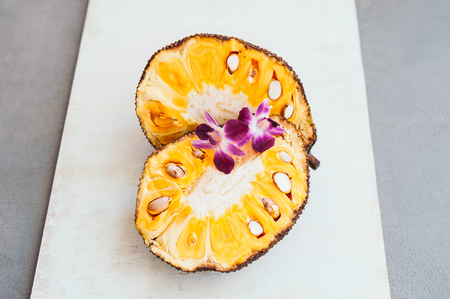 Fresh ripe jackfruit. Tropical fruit with purple orchids on it. Jackfruit segment ready to eat. Organic food. White background. Healthy eating concept