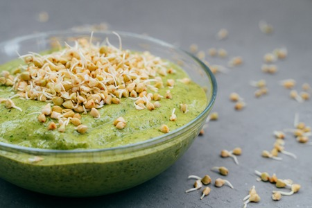 Glass bowl of green fresh smoothie made of organic vegetables with sprouted buckwheat. Healthy clean eating food concept. Raw protein Stok Fotoğraf