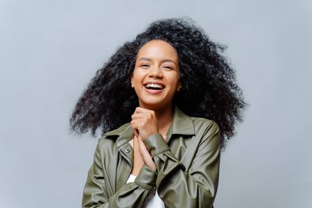 Overjoyed dark skinned curly woman laughs happily, laughs at funny joke, keeps hands pressed together, dressed in fashionable clothes, isolated over grey background. People and positiveness.