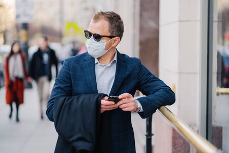 Prosperous businessman in formal wear poses at street, waits for someone, holds mobile phone and sends text messages, wears medical mask during coronavirus outbreak, few people walking outside