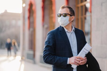Working in pandemic situation. Business worker or entrepreneur wears medical mask for coronavirus protection stands beside office building outdoor holds newspapers concentrated somewhere into distance