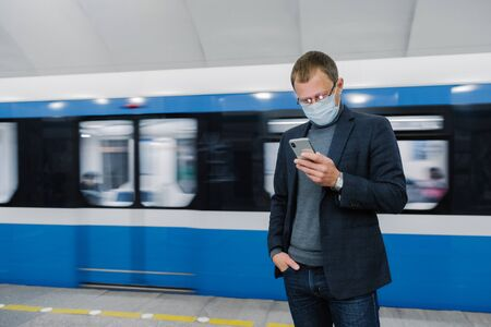 Male passenger wears face mask poses at platform, waits for train, commutes by underground, concentrated in smartphone device, reads news online. Virus awereness in public place. Coronavirus outbreak Imagens