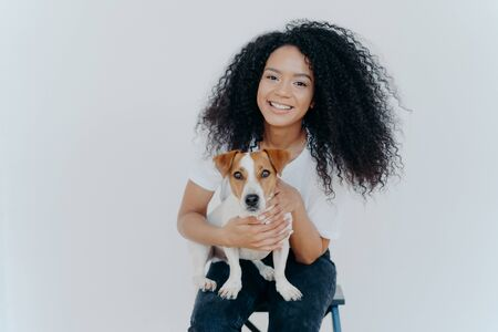 Photo of glad dark skinned female being forever together with pedigree puppy, enjoys leisure at home, sits on chair, isolated over white background. Human and animal connection. Trust and friendship