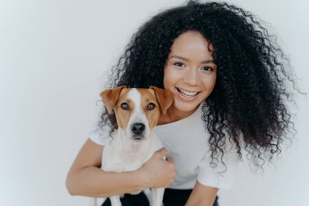 Close up shot of beautiful happy Afro woman with bushy curly hair, embraces favourite dog and have fun together at home, expresses love to jack russell terrier puppy, isolated over white background