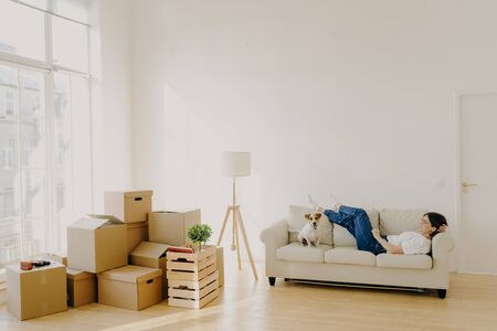 Relaxed female lies on white comfortable sofa with dog, feels tired after relocation and carrying boxes with belongings, lamp stands near, dressed in casual white t shirt, jeans, just arrives in house