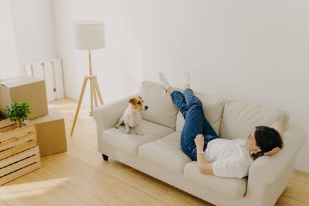 Relocation and mortgage concept. Relaxed brunette woman has rest on comfortable sofa, wears t shirt, jeans and white socks, plays with dog, moves in new apartment, carton boxes with stuff near