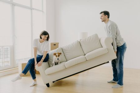 Happy couple carry modern white sofa with dog together, place furniture in living room, care about improvement of interior design, start living in new home, pose in modern apartment, have fun