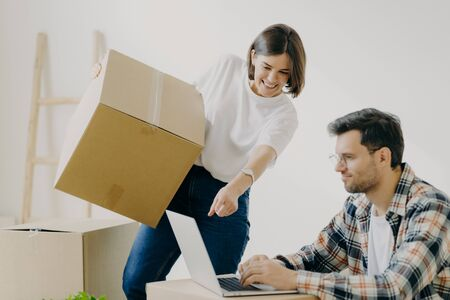 Indoor shot of happy family couple look attentively at laptop computer, search good moving company, carry personal belongings in big cardboard boxes, woman points into display of modern gadget